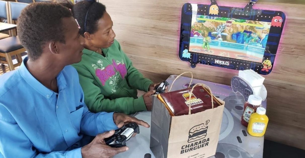 casal jogando videogame hamburgueria