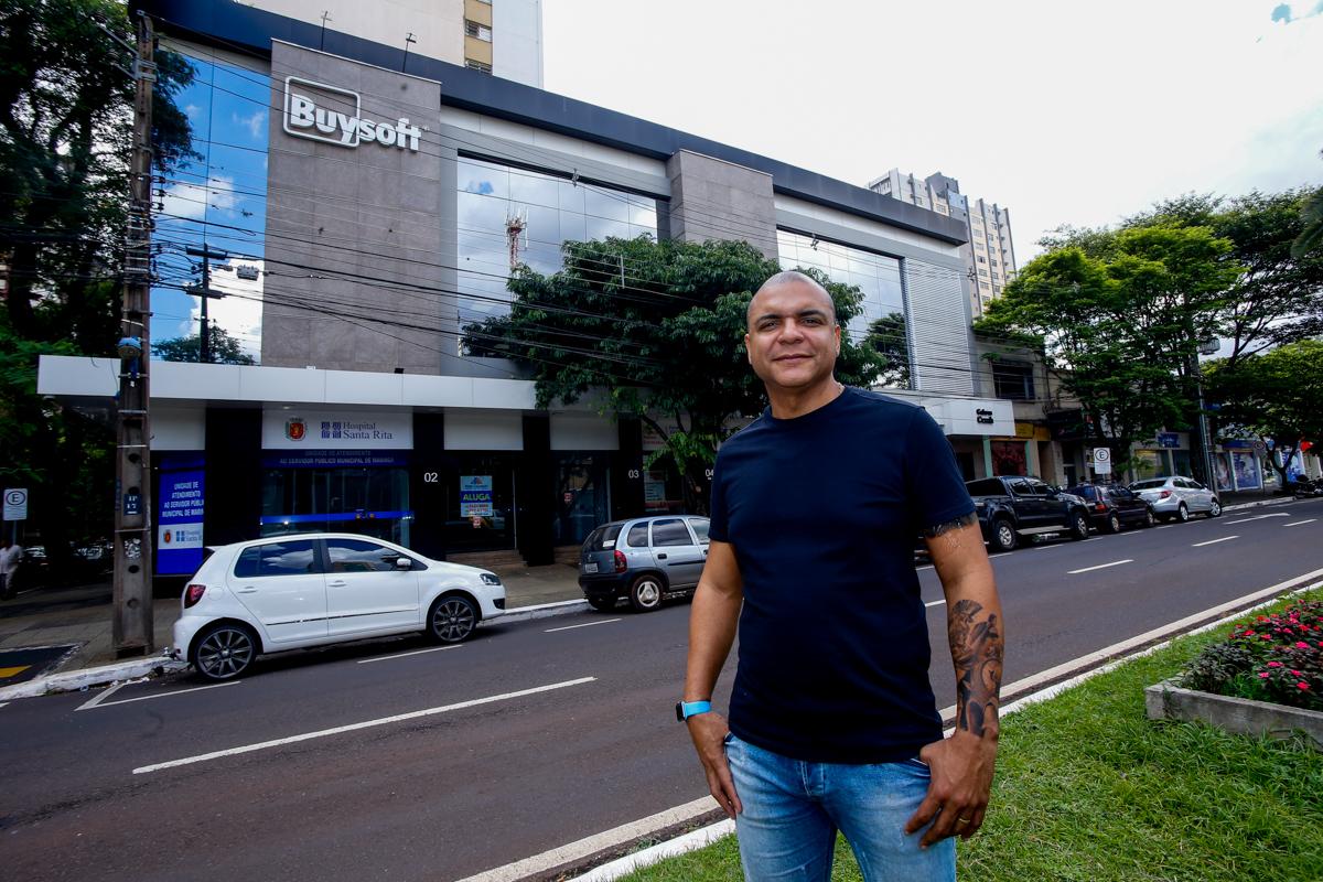 Homem negro em frente a sede de uma empresa milionária