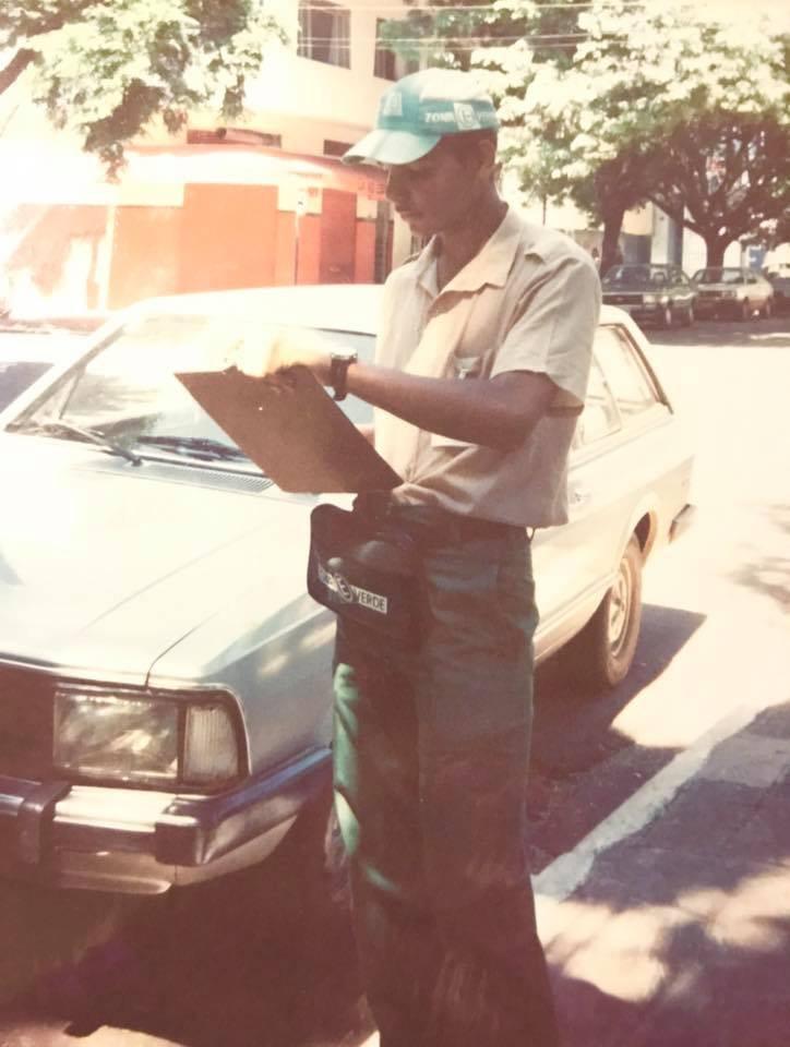 garoto negro com prancheta e em frente a um carro com uniforme de guardinha da Zona Verde