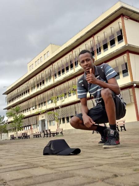 pedreiro elcimar posa para foto em frente a universidade