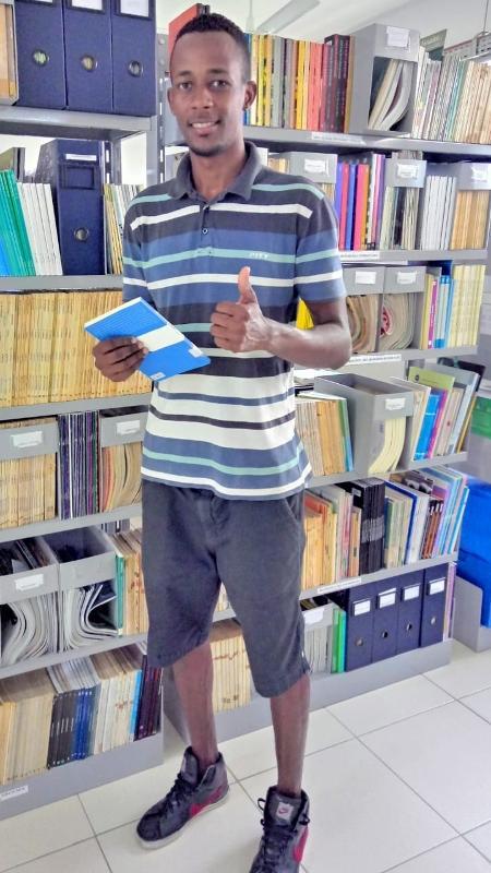 pedreiro elcimar posa para foto na biblioteca da universidade