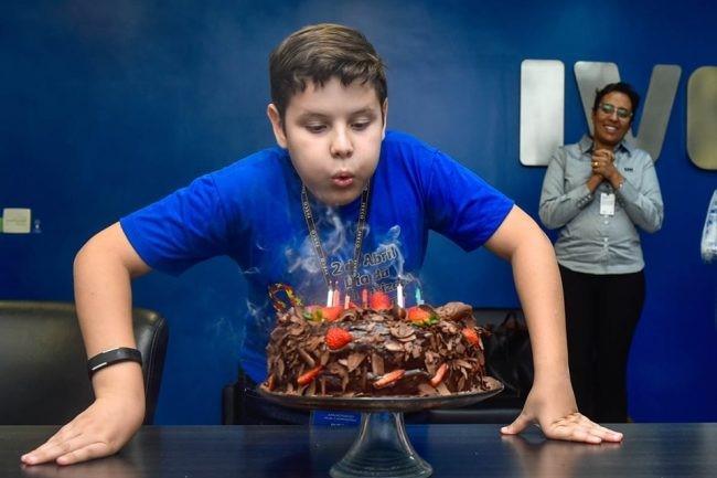menino apaga velas bolo aniversário