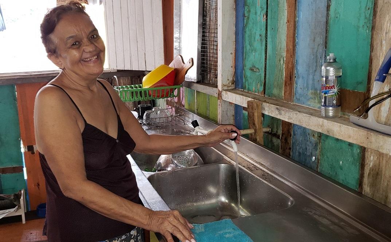 moradora casa palafitas recebe água potável torneira