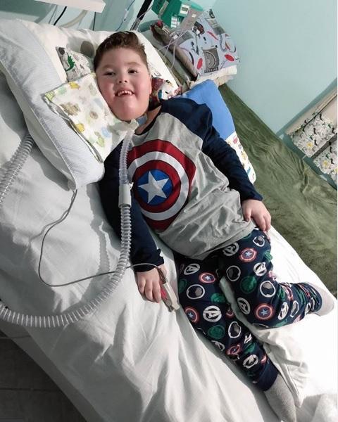 menino doença rara deitado cama