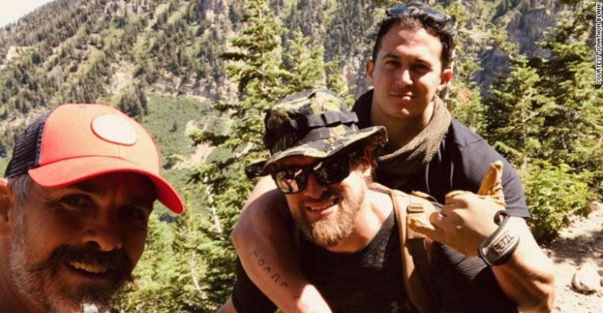 homem carregando amigo perdeu pernas topo montanha