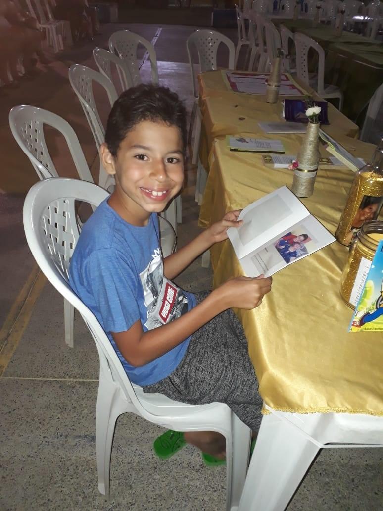 menino segurando livro