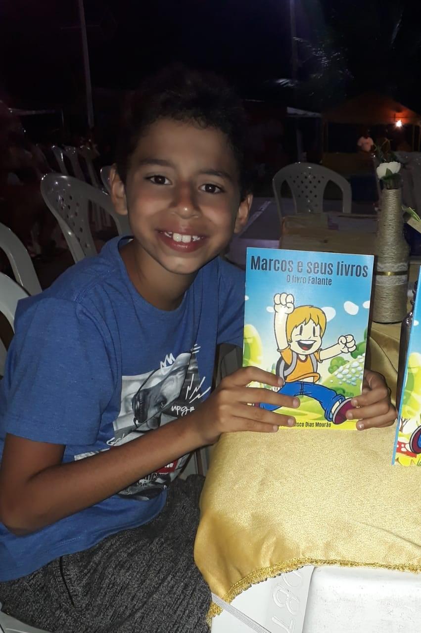 menino segurando livro que ele escreveu