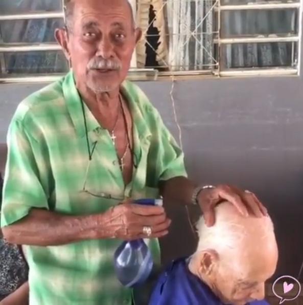 barbeiro borrifando água cabelo idoso