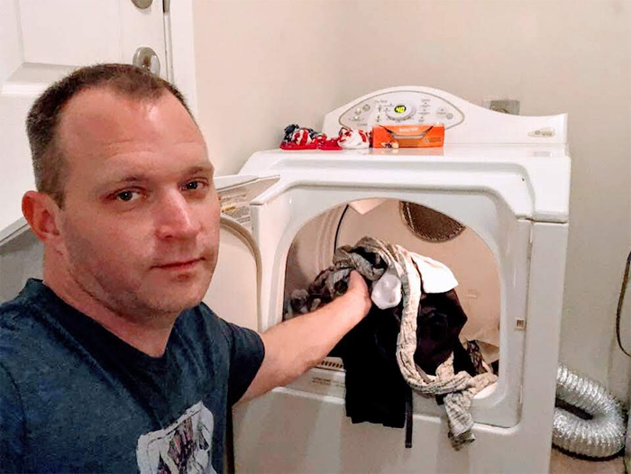 homem colocando roupa suja máquina lavar