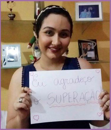 mulher segurando um cartaz com os dizeres eu agradço o SuperAção