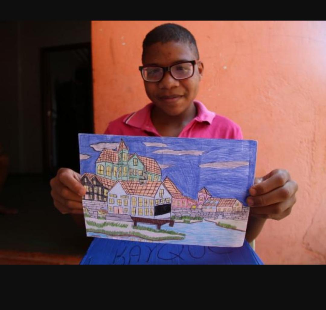 Jovem que vende desenho no portão de casa mostrando uma arte dele