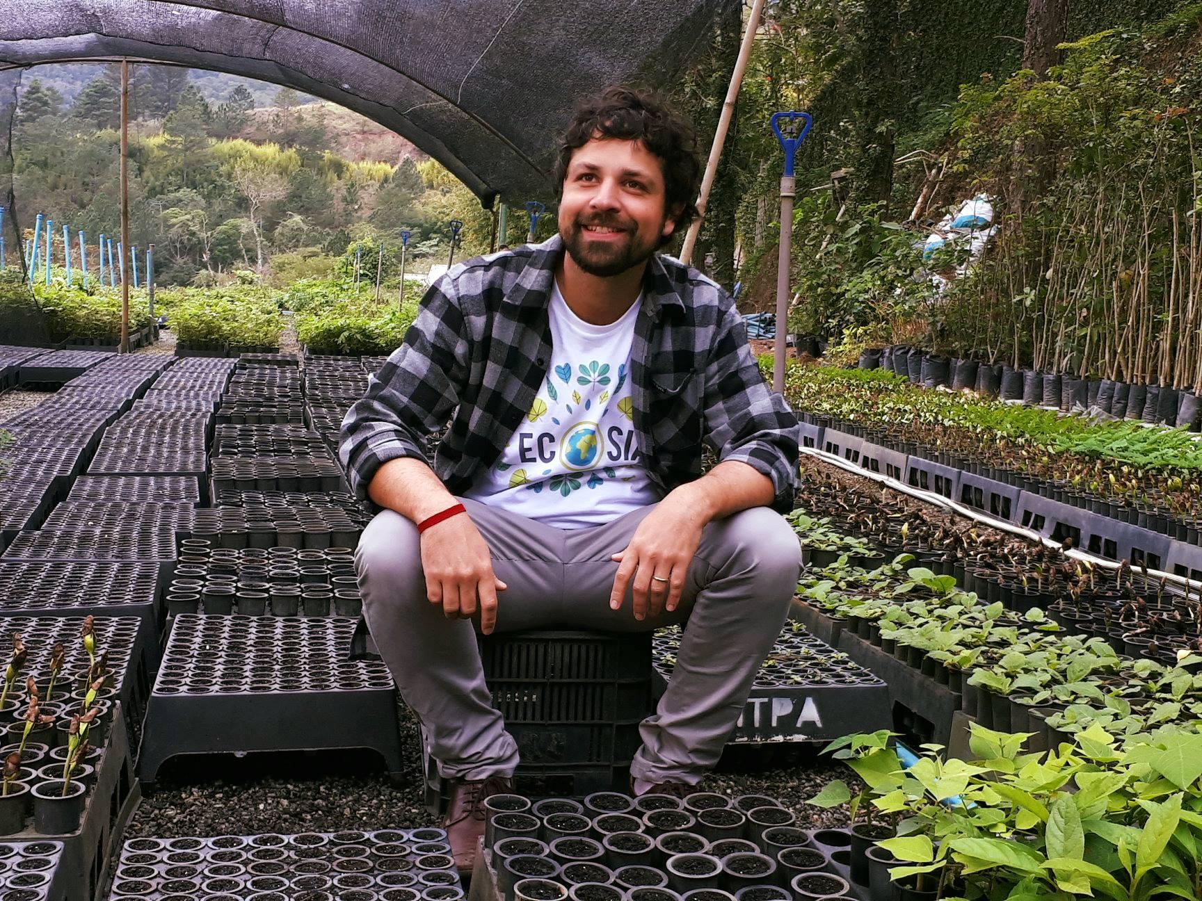 Ativista Mauricio Ruiz sentado em meio da mudas de árvores do ITPA