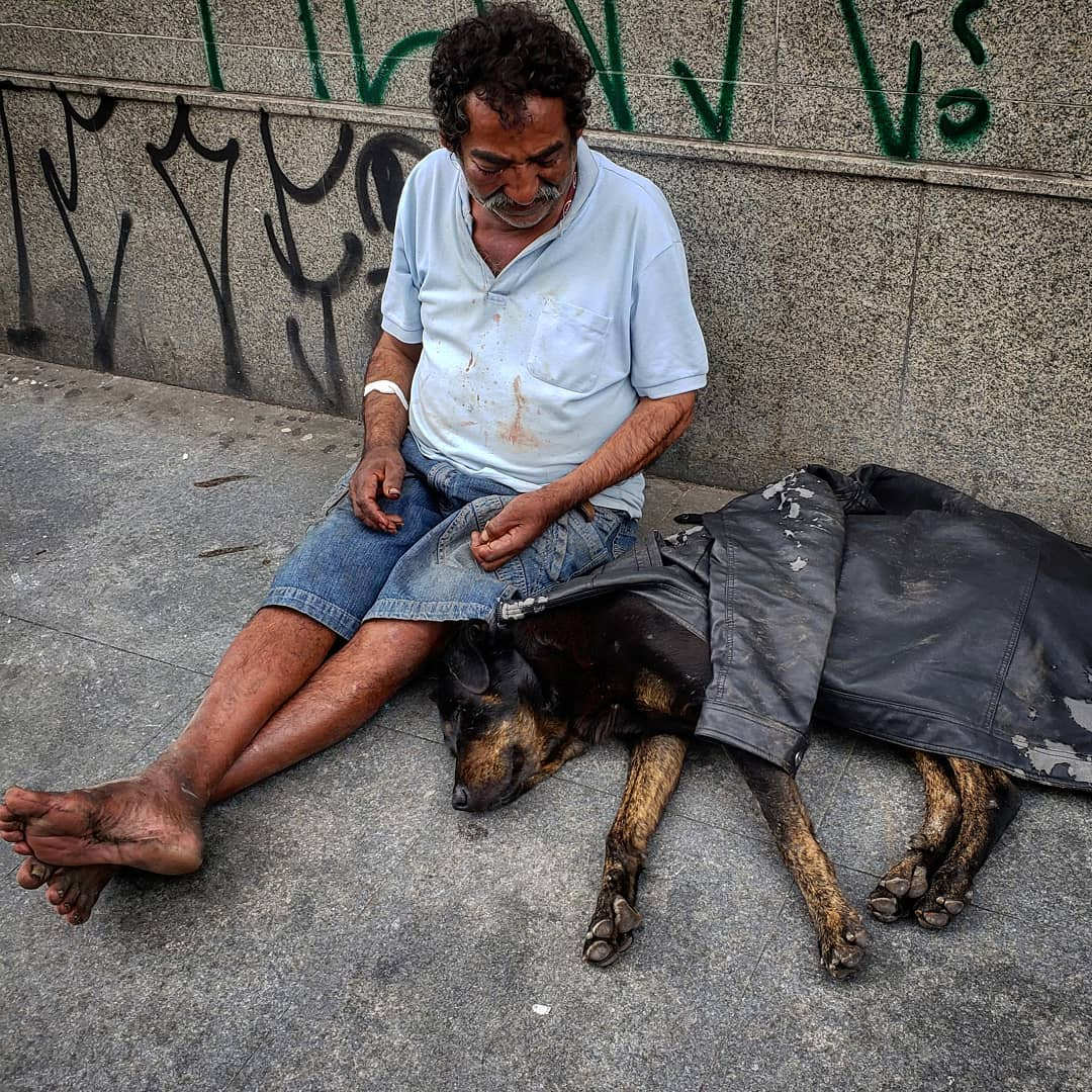 morador de rua sentado na calçada ao lado do seu cachorro coberto pela sua jaqueta