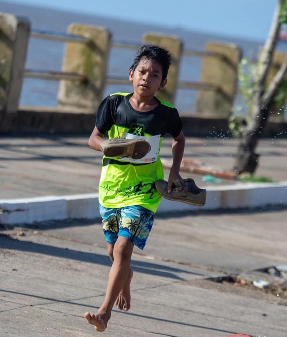 garoto correndo descalço em corrida de rua