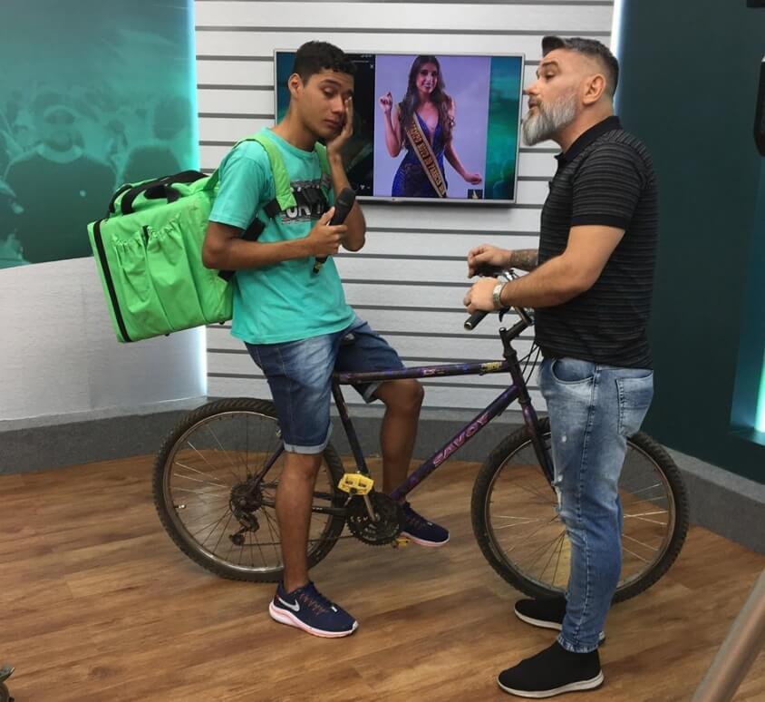 entegador do Uber Eats em programa de TV com a sua bicicleta
