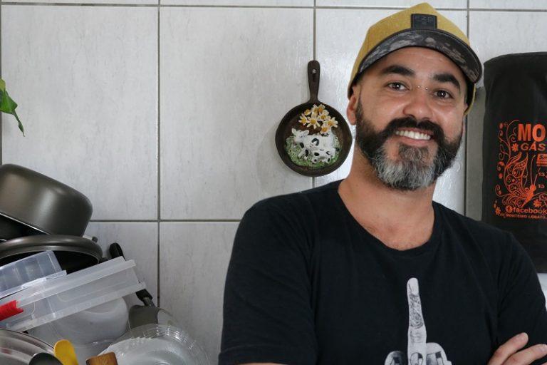 homem posa sorrindo para foto de boné amarelo e camiseta preta