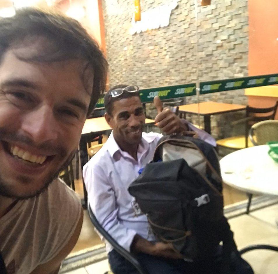 empresário ao lado do morador de rua que vende balas personalizadas