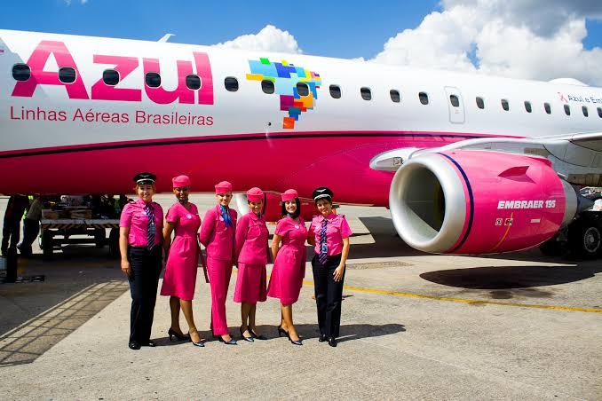 aeromoças e pilotos vestidos de rosa em frente ao avião rosa para o mês Outubro Rosa