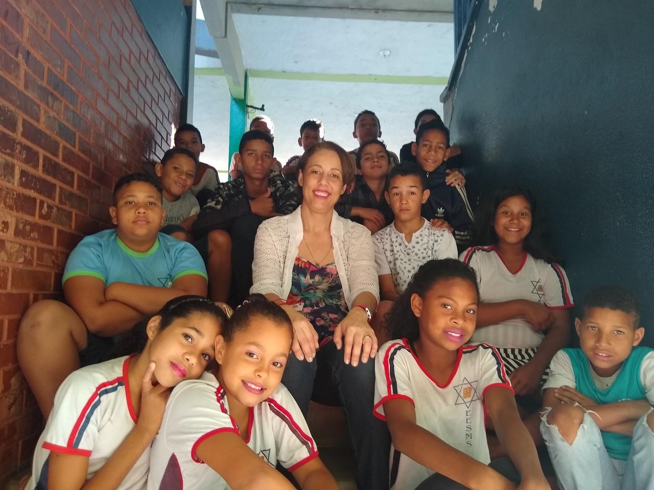 professora com os alunos e escadaria da escola