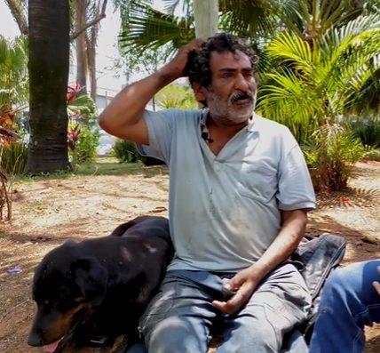 morador de rua sentado ao lado do seu cachorro