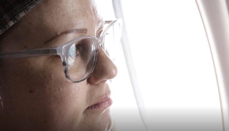 mulher com câncer de mama olhando a janela de um avião