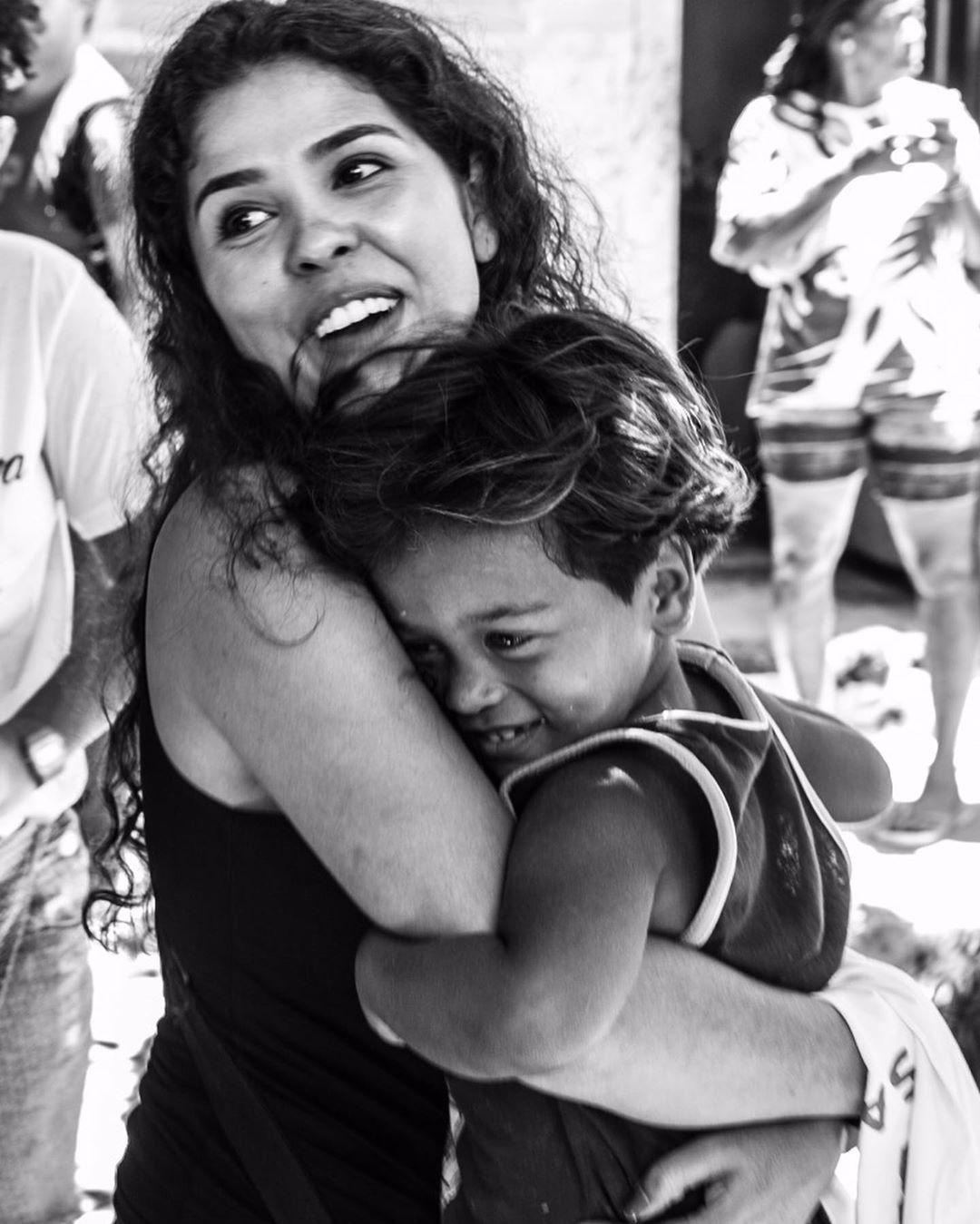 fundadora do projeto A Arte Salva em Jd. Gramacho abraçando uma criança