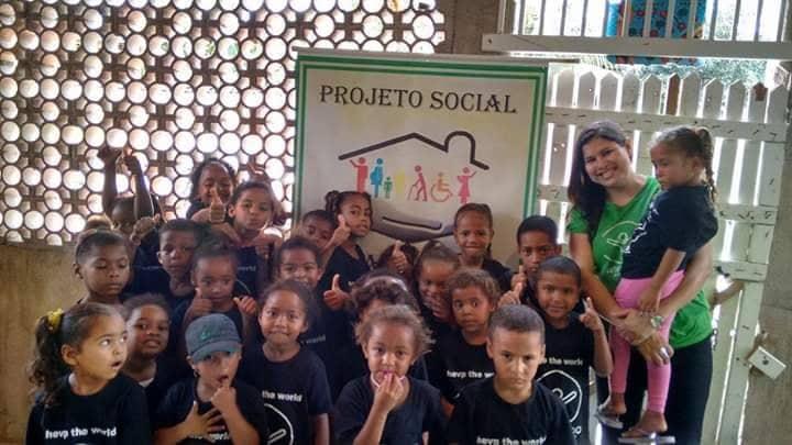 crianças em frente a placa do Instituto Amparando