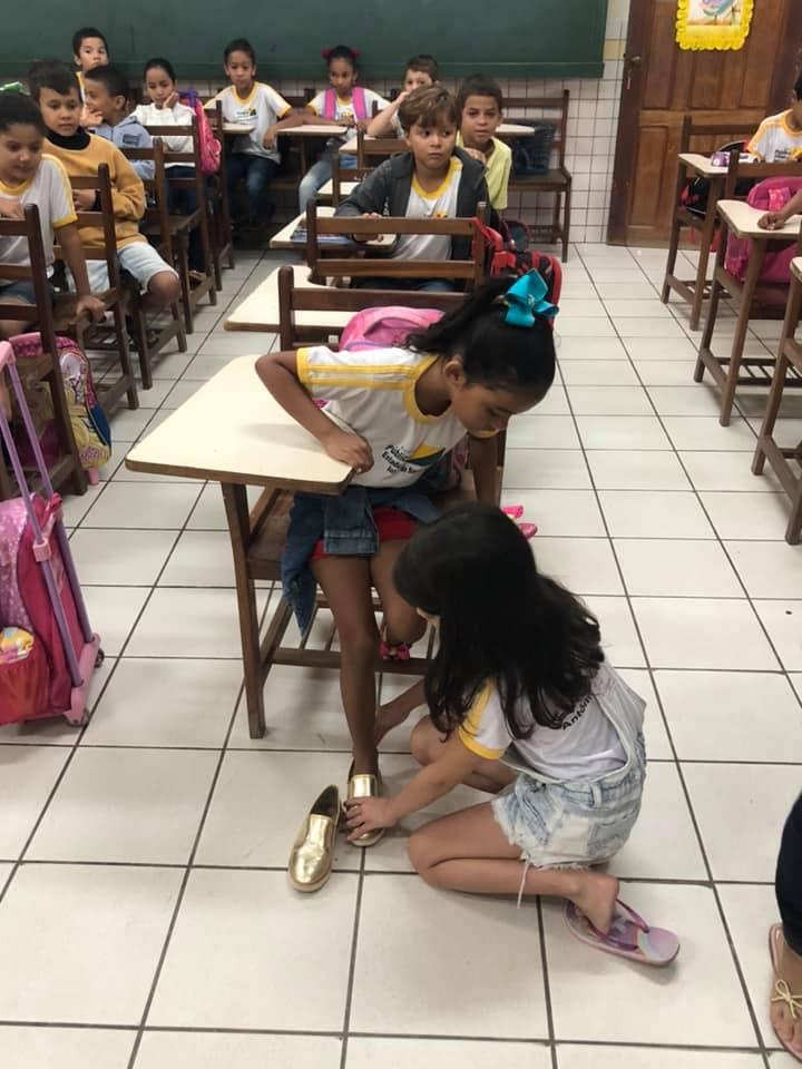 professora relato menina doa sandália ajoelha colega