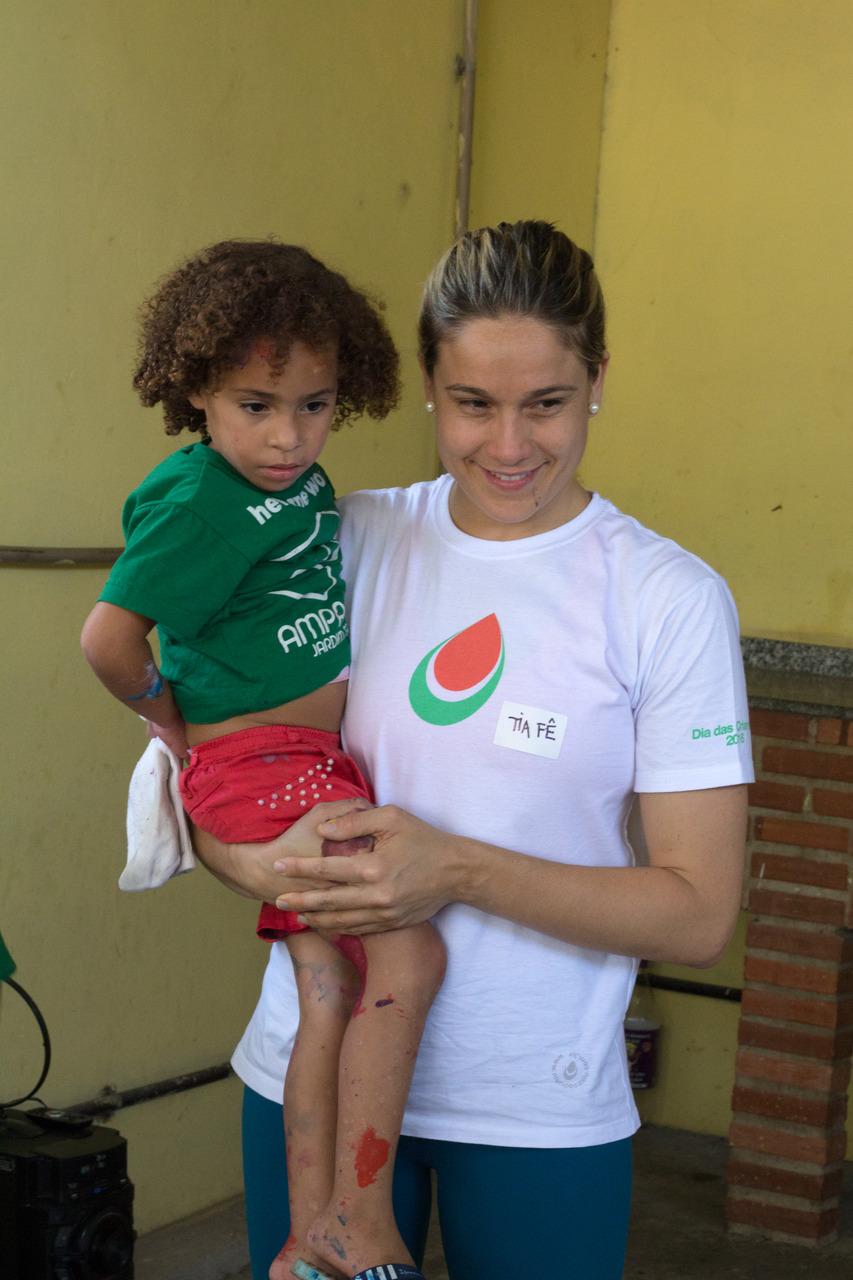 Fernanda Gentil carregando uma criança do Instituto Amparando