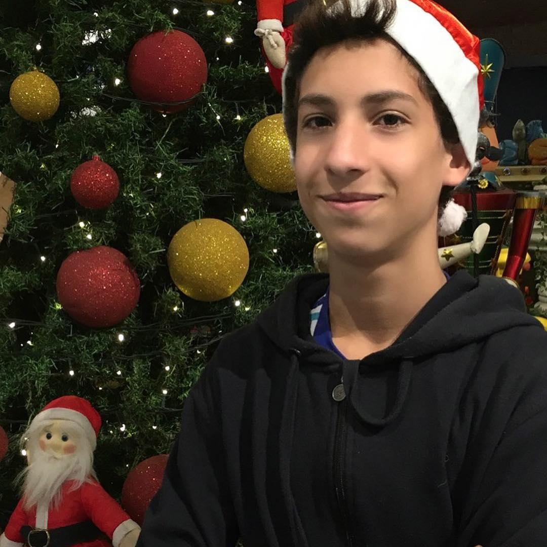 jovem da campanha para apadrinhar idosos em frente a árvore de Natal