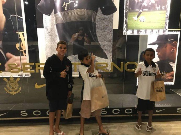 meninos ajudados por torcedor corinthiano em frente a loja do Corinthians