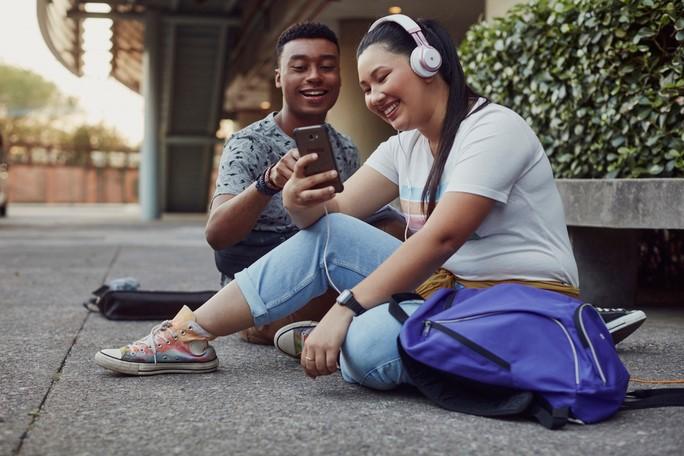 dois jovens olhando celular sentados