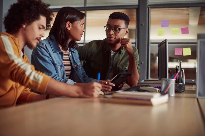 três jovens mesa escritório mexendo tecnologias digitais