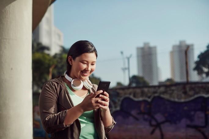 jovem usando celular sorrindo