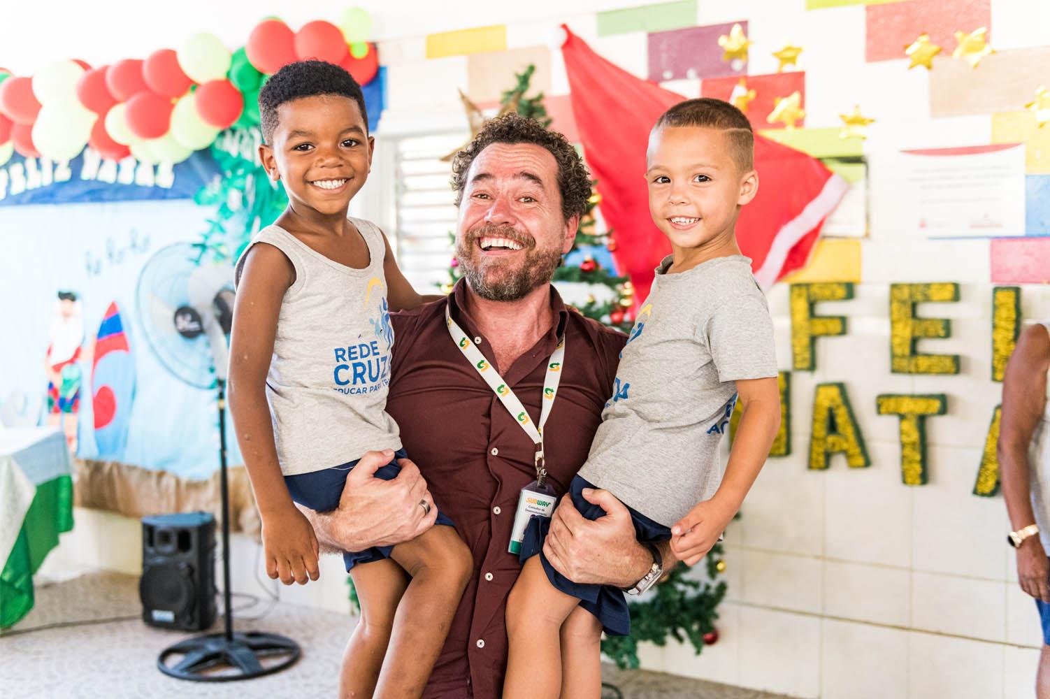 homem segurando duas crianças colo evento subway