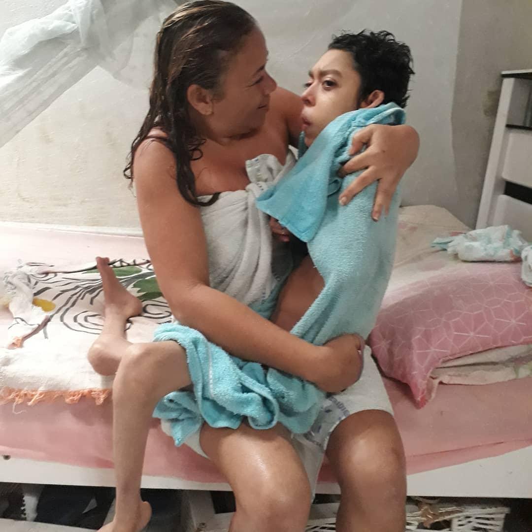 mãe segurando o filho especial no colo