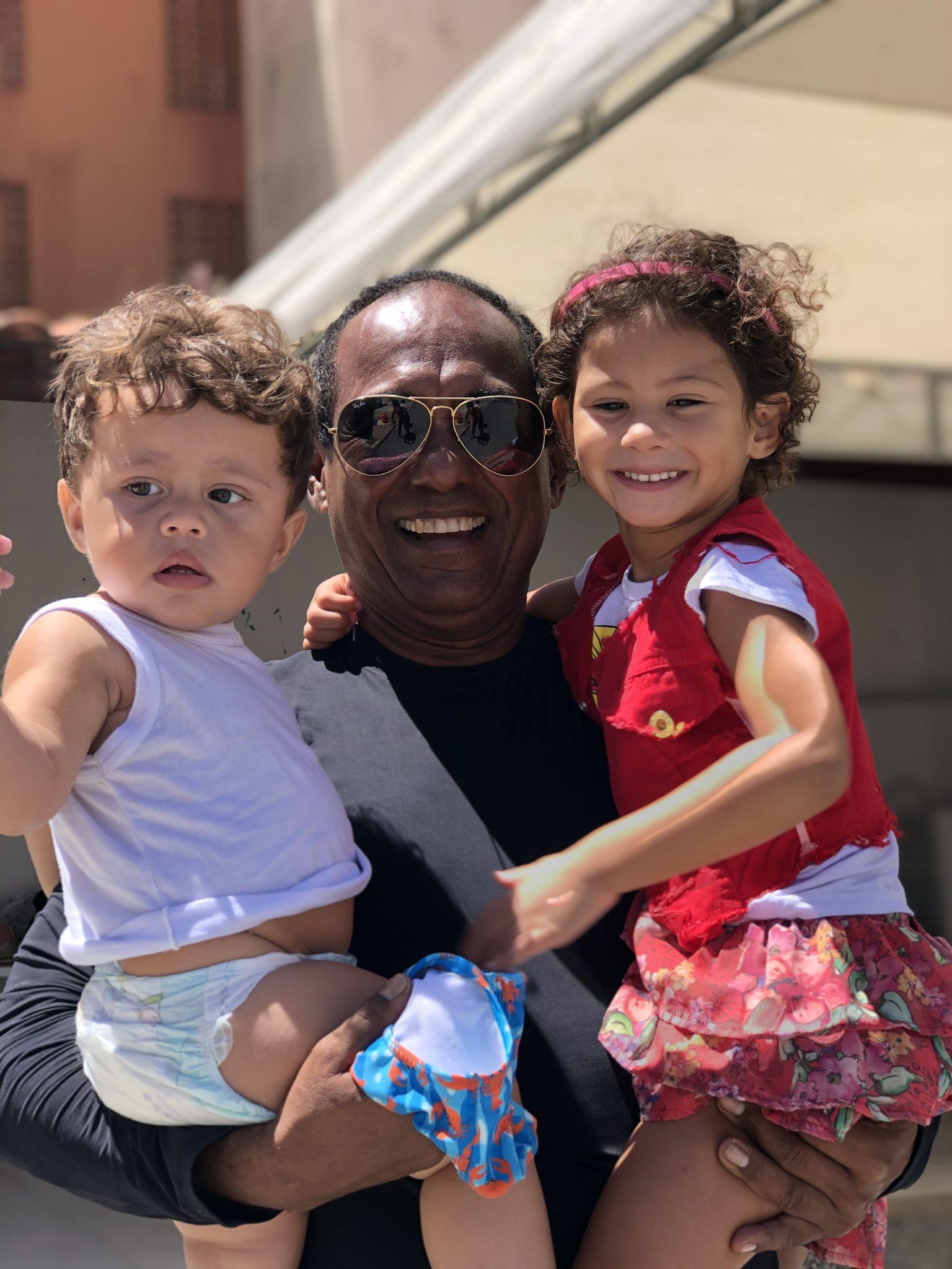 homem que realiza festa na piscina segurando duas crianças