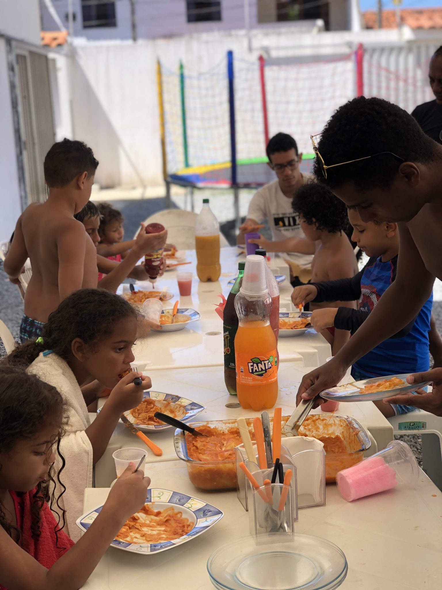 crianças comendo e festa na piscina realizada por homem