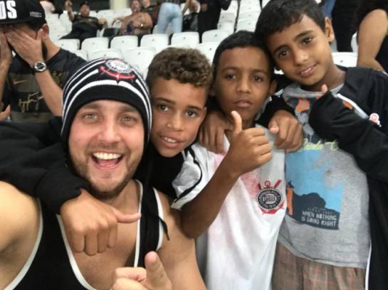 torcedor corinthiano com meninos que ele ajudou em jogo do Corinthians