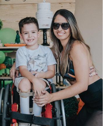 mãe e filho que faz tratamento fisioterapeuta mielomeningocele