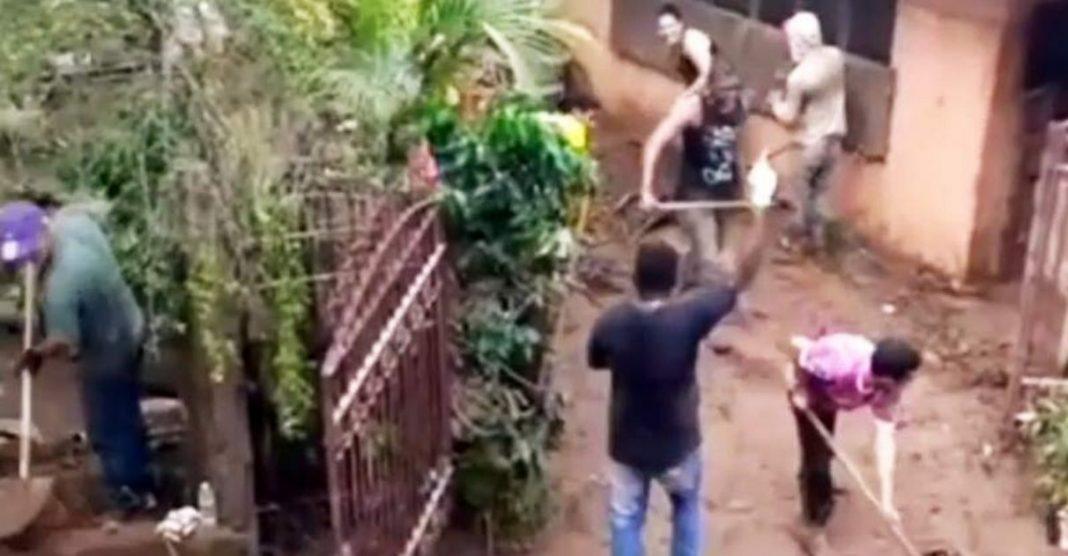 Moradores de Sabará retiram lama de suas casas cantando e dançando