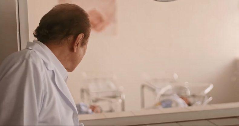 médico que doa uma muda de árvore para cada bebê que traz ao mundo olhando para o berçário