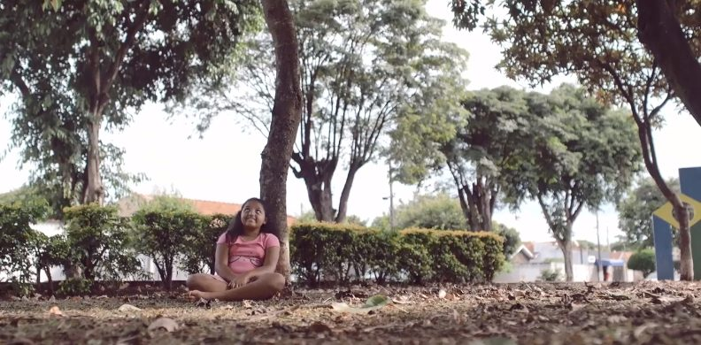 criança sentada sob uma árvore do projeto Plantar do doutor Calixto