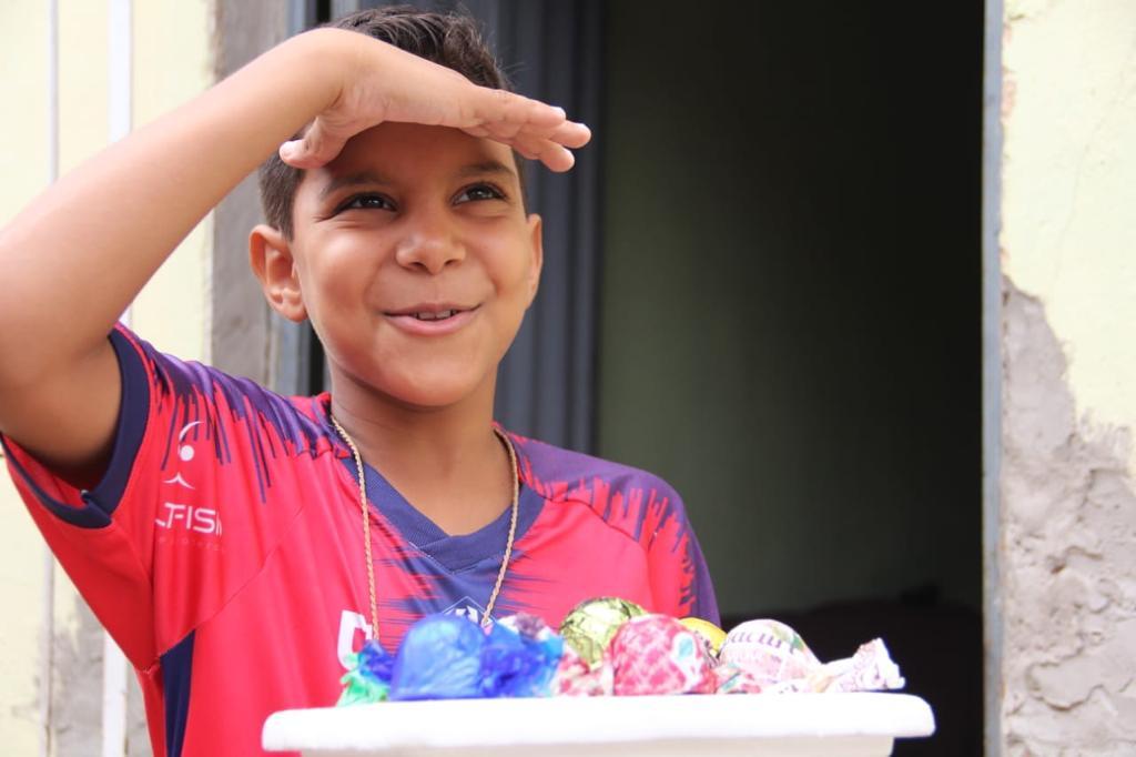 menino Lzinho segurando os bombons que ele vende