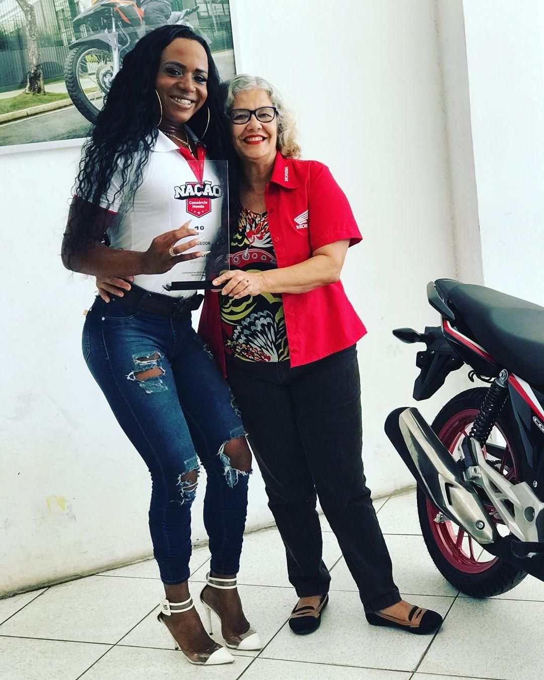 Mulher trans com prêmio Honda ao lado de funcionária