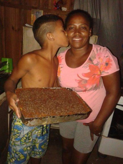 Garoto que ganhou bolo de aniversário simples beijando a mãe por surpresa