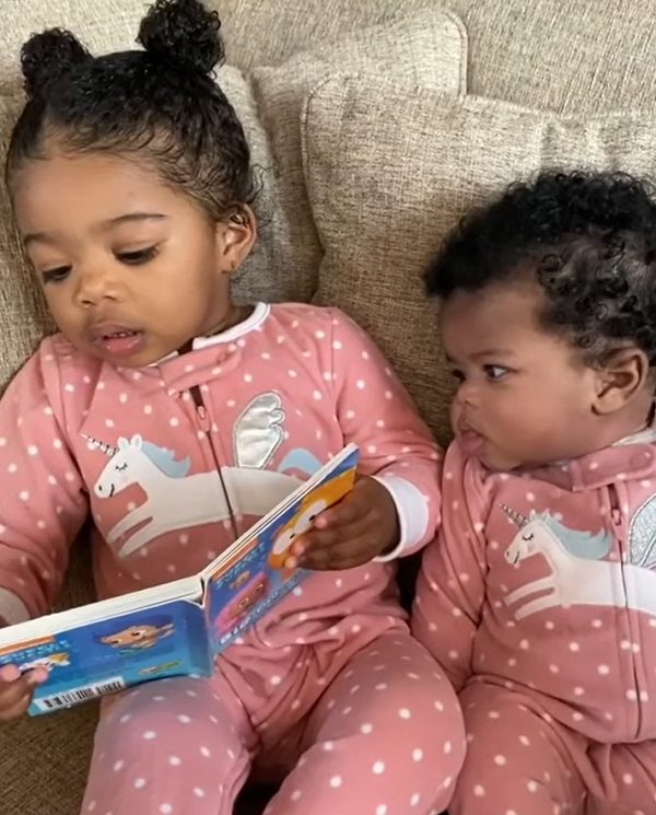menina lê história para irmã imitando a mãe