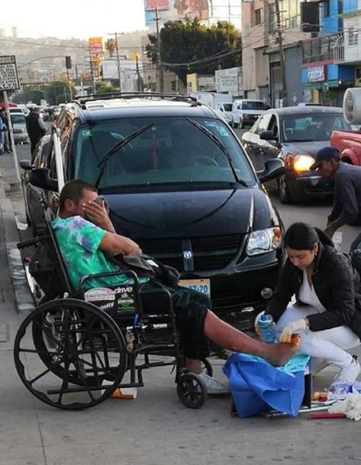 Enfermeira trata feridas de morador de rua no meio da rua