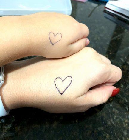 Mãos de mãe e filha com desenho de coração que mãe fe para filhar matar saudade dela na escola e depois flagrou menina beijando o coração