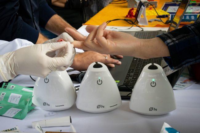 Paciente tendo o dedo furado para teste do coronavírus com aparelho que dá resultado em 15 minutos